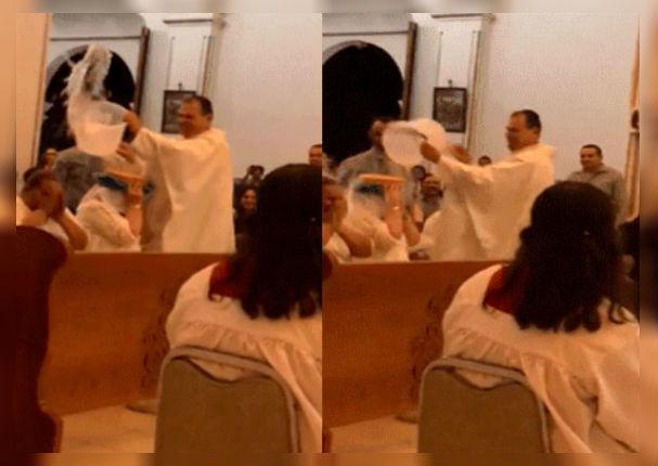 Sacerdote limpia de pecados a sus fieles con 'baldes' de agua bendita